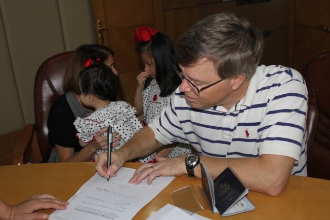 Daddy Signing Adoption Paperwork